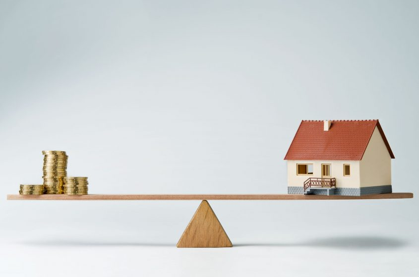 A model house balances on a seesaw with stacks of coins on the other side.