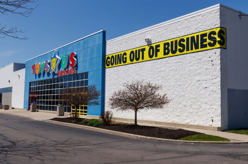 A sign reads 'Going Out of Business' on the outside of a Toys R Us storefront.