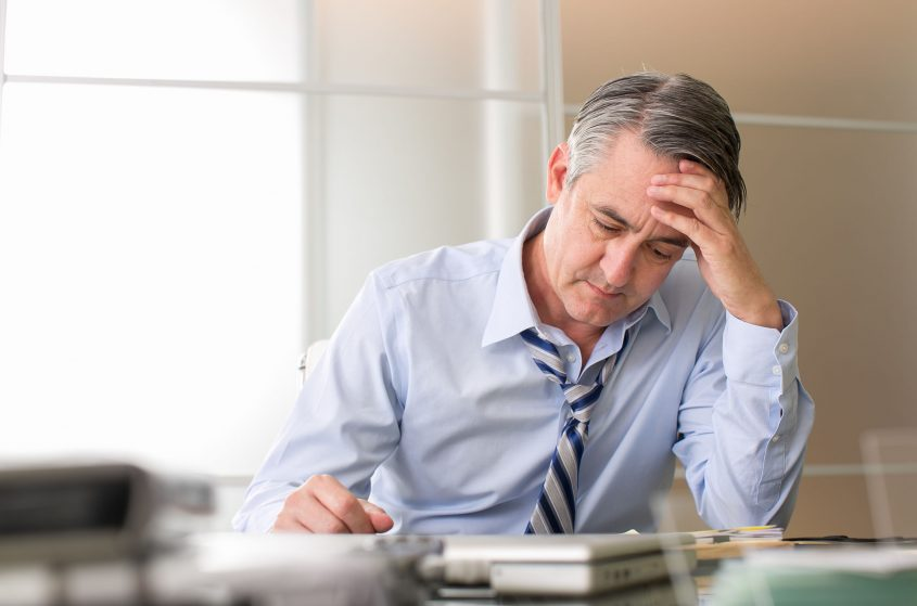 A stressed man leans over a desk.