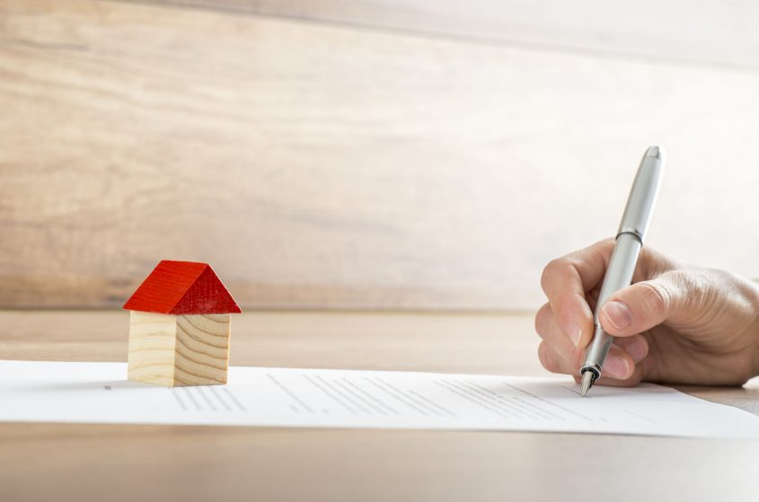A small wooden house sits on top of mortgage papers that a hand is signing.