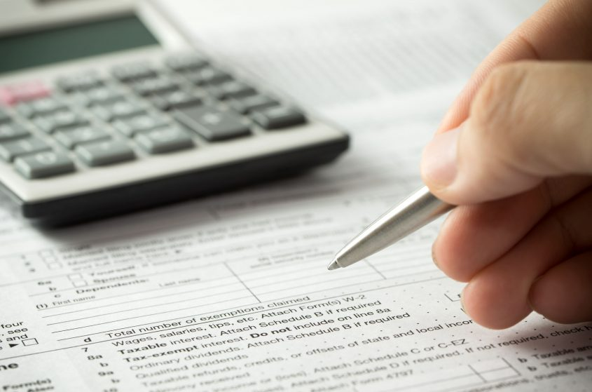 A hand holds a pen over a tax form with a calculator on the desk.