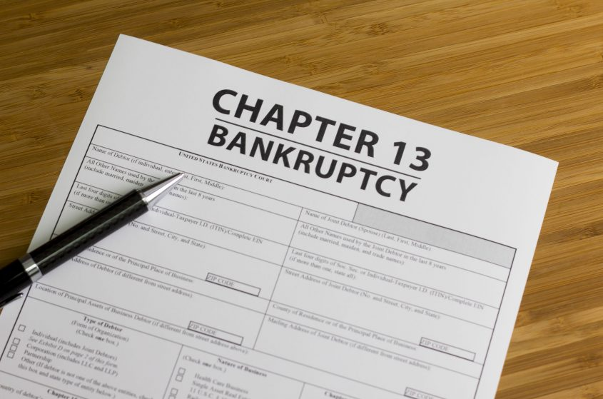 A pen sits on a Chapter 13 Bankruptcy form