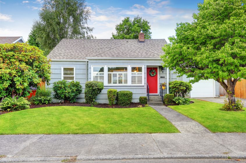 small colonial house with a red door surrounded by trees.
