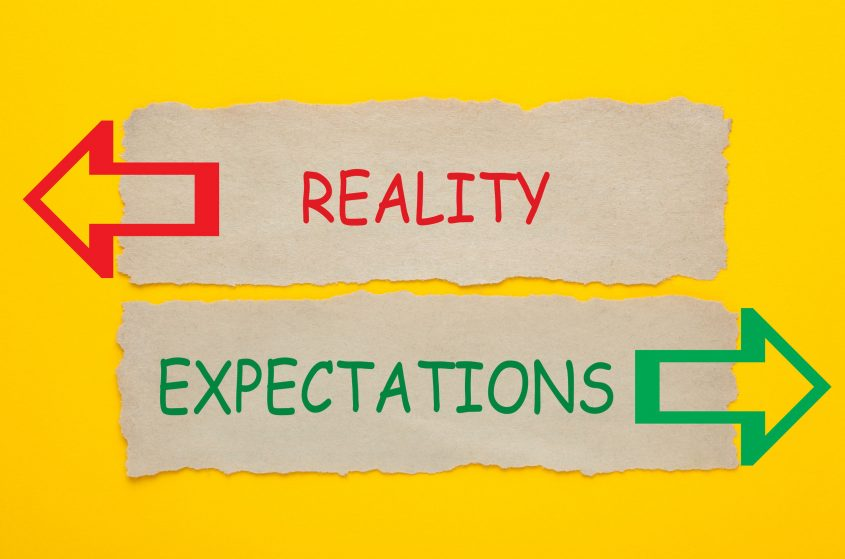 two signs read reality and expectations, respectively. They point in two different directions.