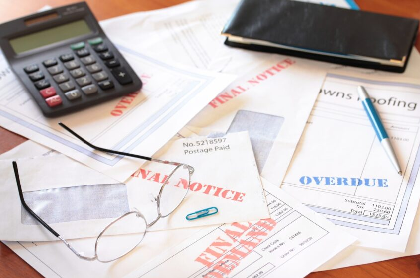 business insolvency concept of a lot of unpaid bills under glasses and a calculator
