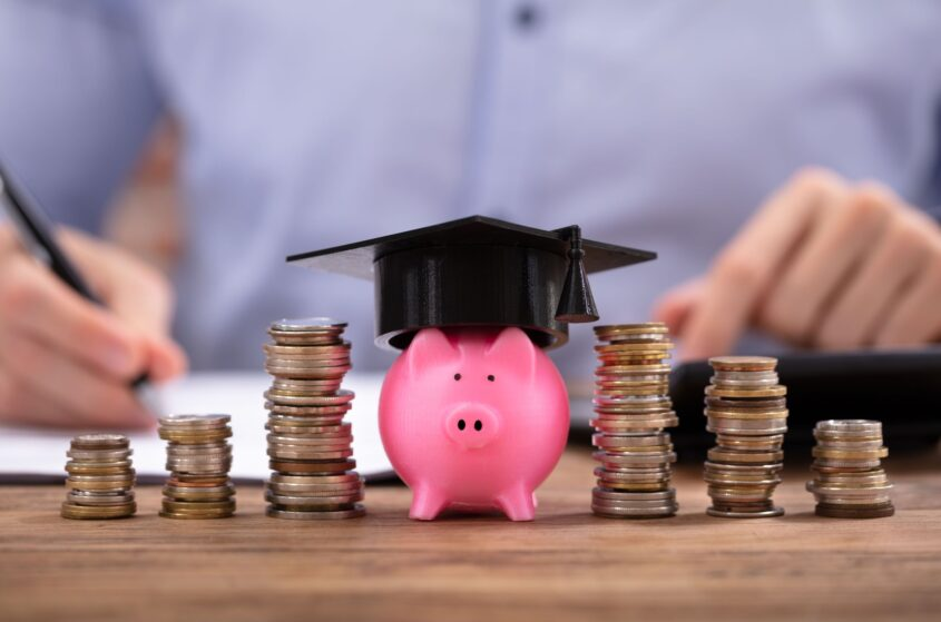 piggy bank next to coins with school graduation hat representing how to pay student debt