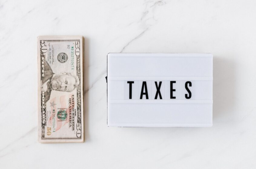 """""""TAXES"""" sign next to dollar bills of 50$ representing the importance of paying taxes in debt management"""