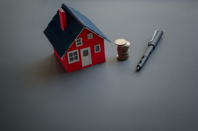 Small red toy house next to coins and a pen representing that it is time for a loan modification on the mortgage